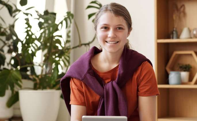 Girl smiling while holding iPad