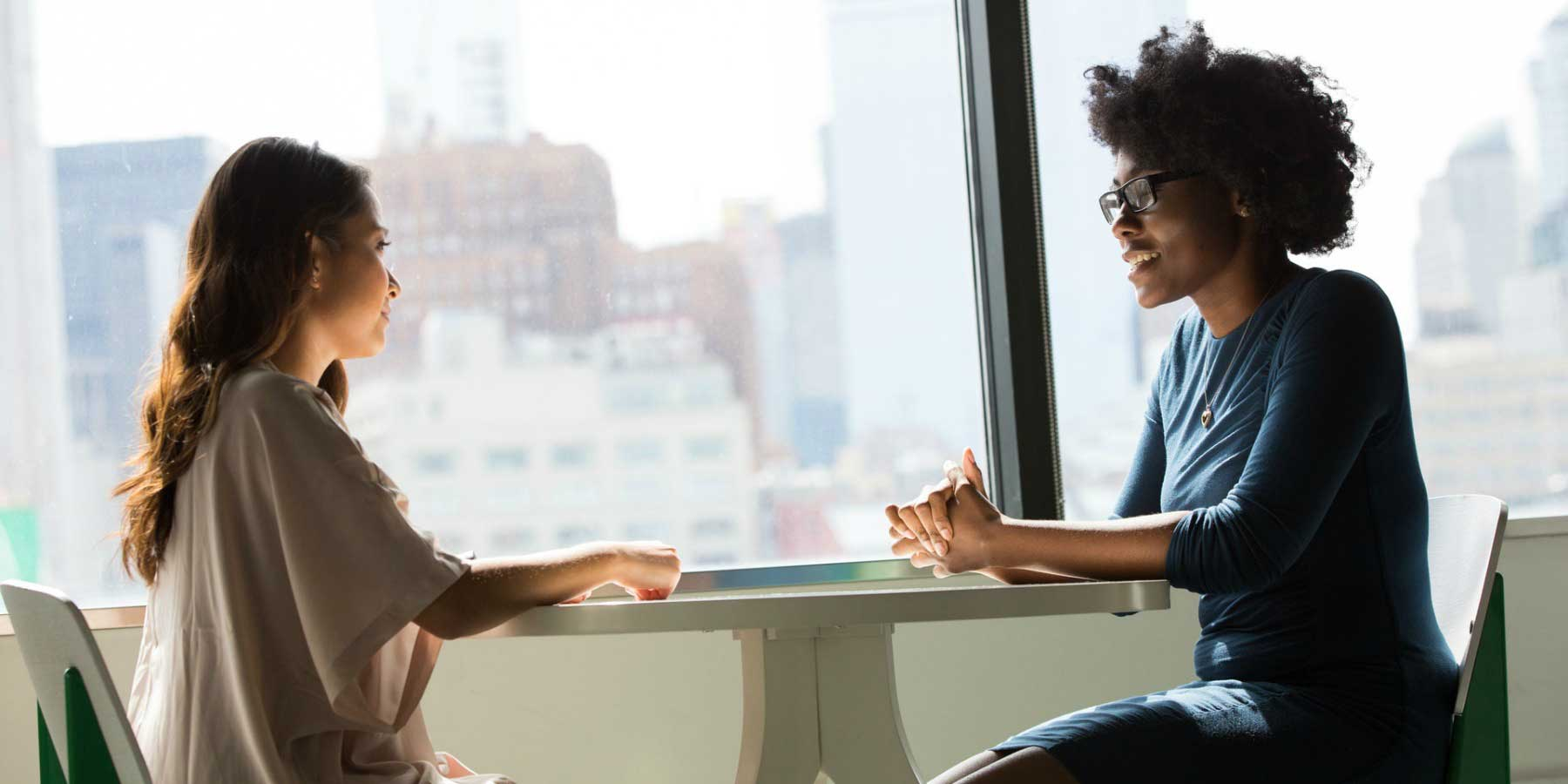 two women talking to each other at table
