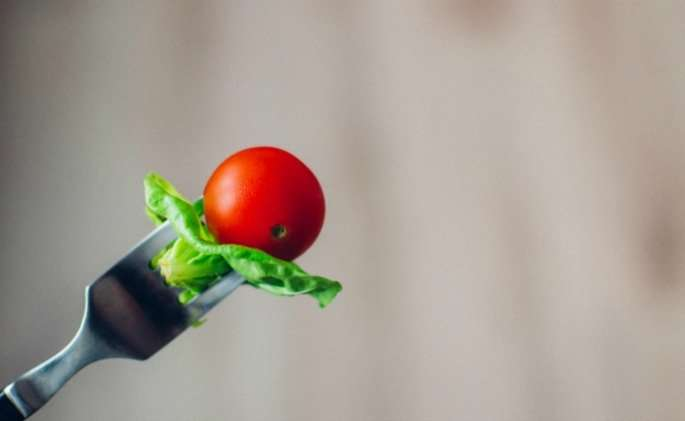 tomato and lettuce on fork
