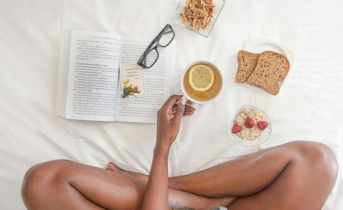 Woman sitting on bed with food